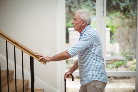 Älterer Mann klettert oben mit Spazierstock zu Hause