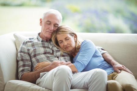 Senior couple relaxing on sofa in living room at home Stock Photo