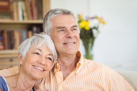 Smiling senior couple sitting together on sofa in living room at home Stock Photo