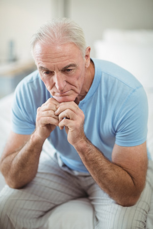 Tense senior man sitting on bed in bedroom at home