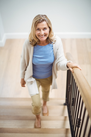 Portrait of smiling senior woman climbing upstairs at home Stock Photo