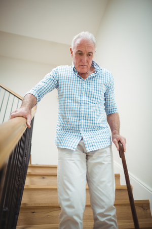 ageing process: Senior man climbing downstairs with walking stick at home Stock Photo