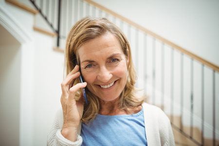 Portrait of smiling senior woman talking on mobile phone at home