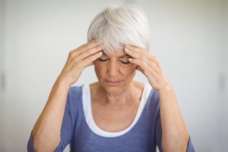 ageing process: Senior woman having headache at home