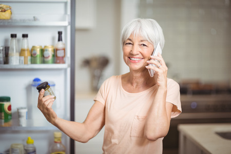 Senior woman looking at jar while talking on mobile phone in kitchen at home