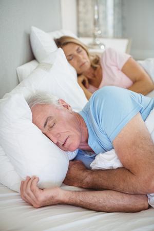nightwear: Senior couple sleeping on bed in bedroom