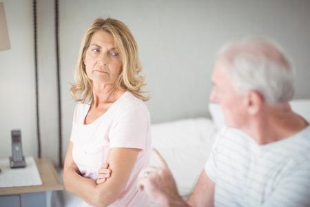 uneasy: Worried senior woman sitting on bed in bedroom