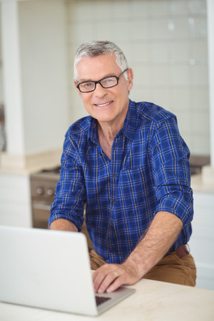 Portrait of senior man using laptop in kitchen at home Stock Photo