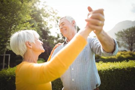 Happy senior couple dancing in park