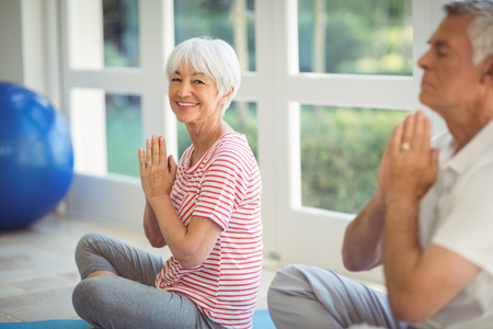 Senior couple performing yoga on exercise mat at home