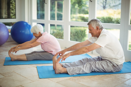 운동 매트 집에서 스트레칭 운동을 수행하는 수석 커플 스톡 콘텐츠