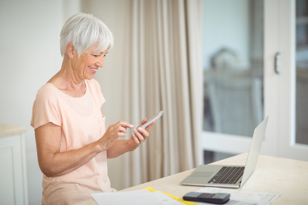 Senior woman using mobile phone in kitchen at home Stock Photo