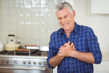Senior man suffering from heart attack in kitchen at home Banco de Imagens