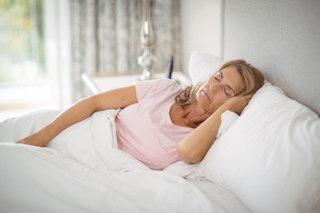 ageing process: Senior woman sleeping on bed at home Stock Photo