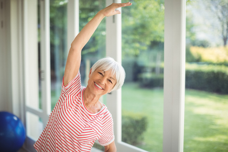 Portrait of happy senior woman performing stretching exercise at home