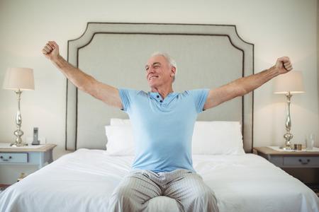 침대에서 일어나서 그의 팔을 스트레칭하는 시니어 남자 스톡 콘텐츠