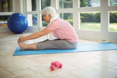 Happy senior woman performing stretching exercise at home Stock Photo