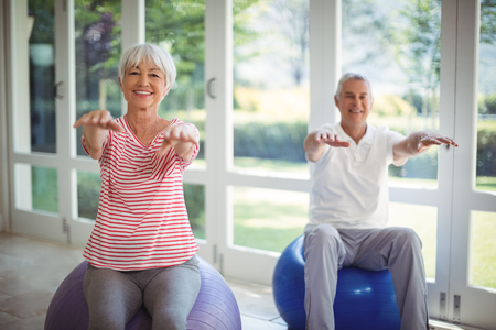 Senior couple performing stretching exercise on fitness ball at home