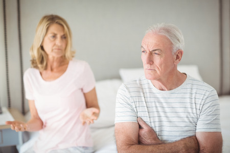 argues: Worried senior man sitting on bed in bedroom Stock Photo