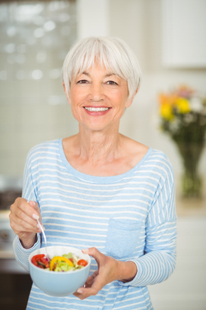 Portrait of happy senior woman holding bowl of vegetable salad in kitchen Stock Photo