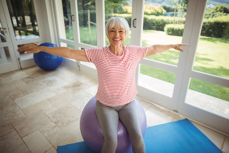 ageing process: Senior woman performing stretching exercise on fitness ball at home Stock Photo