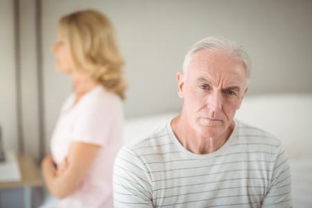 Worried senior man sitting on bed in bedroom Stock Photo