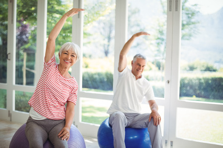 ageing process: Senior couple performing stretching exercise on fitness ball at home
