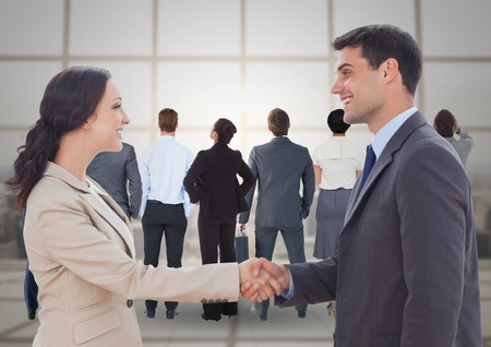 Digital composite of Handshake in front of business people at window Stock Photo