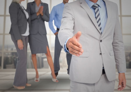 well dressed: Digital composite of Handshake in front of business people at window Stock Photo
