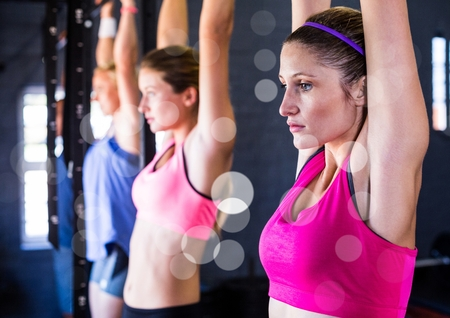 Digital composite of Fitness women doing pull ups with bokeh in a gym