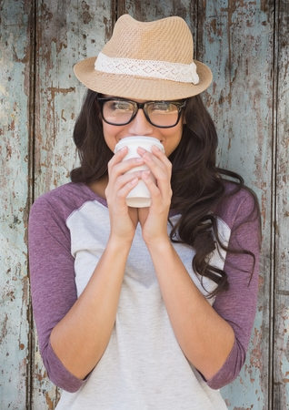 Digital composite of Woman with coffee and hat against wood panel Stock Photo
