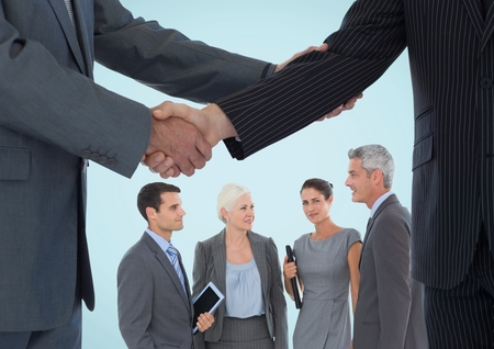 Digital composite of Handshake in front of business people against blue background photo