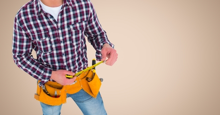 Digital composite of Carpenter with measuring tape against cream background