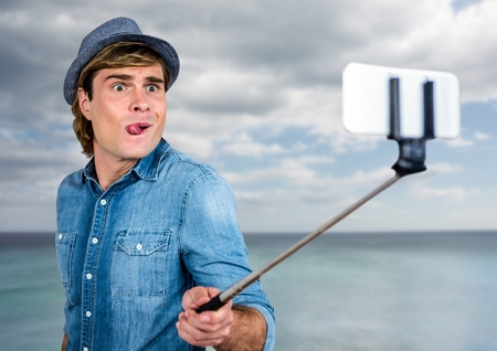 Digital composite of Man with selfie stick in front of sea Stock Photo