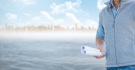 Digital composite of Architect Torso holding plan against sea and city background