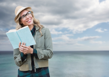 Digital composite of Woman with book in front of sea