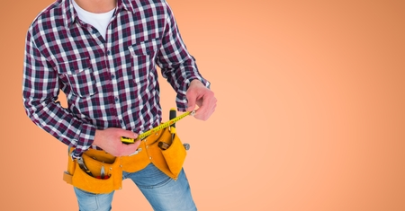 Digital composite of Carpenter with measuring tape against orange background
