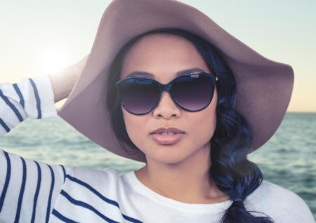Digital composite of Woman in summer hat against sea with flare