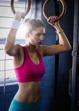 Digital composite of Woman doing pull ups with flare in a gym