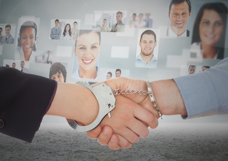 Digital composite of Handshake with handcuffs in front of sky with business people