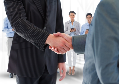 Digital composite of Handshake in front of business people in office photo