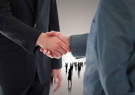 Digital composite of Handshake in front of silhouette business people photo