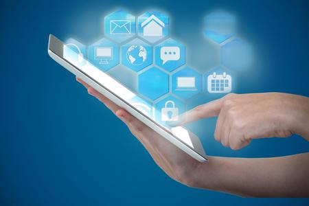 Hands using digital tablet against white background against blue Stock Photo