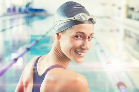 Pretty swimmer by the pool smiling at camera against graphic image of flare