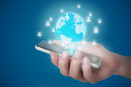 Cropped image of person holding mobile phone against blue