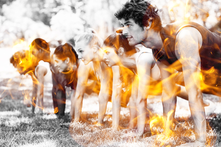 Fire flames against group of fitness people doing push ups in park