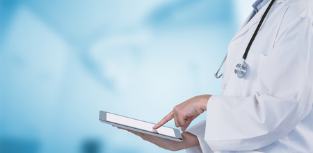 Midsection of female doctor using digital tablet against dental equipment Stock Photo