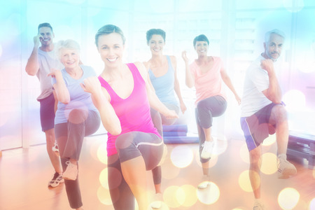 Smiling people doing power fitness exercise at yoga class against abstract background photo
