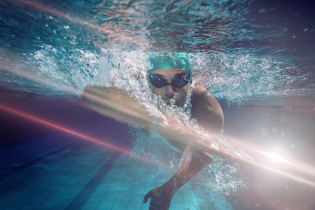 Fit swimmer training by himself against graphic image of flare