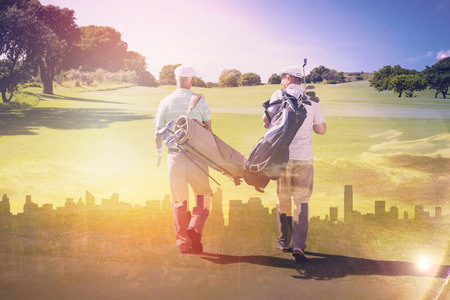 Picture of city by sunrise against rear view of friends walking together at golf course Stock Photo